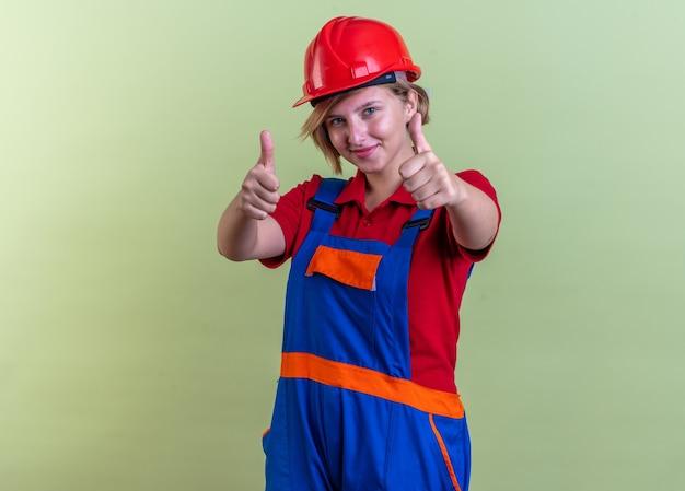 オリーブグリーンの壁に分離された親指を見せて制服を着た若いビルダーの女性を喜ばせる