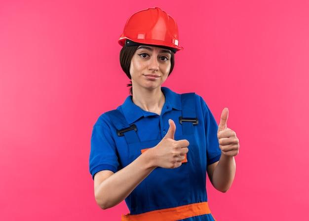 분홍색 벽에 격리된 엄지손가락을 보여주는 제복을 입은 젊은 건축업자 여성