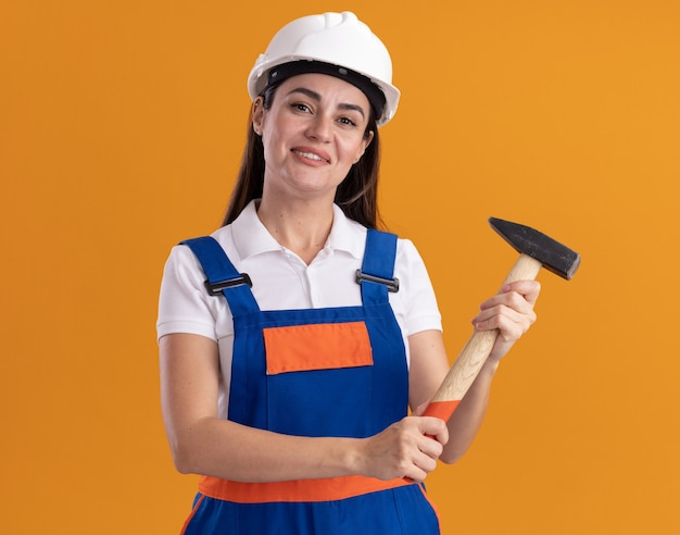 Felice giovane donna costruttore in uniforme che tiene martello isolato sulla parete arancione