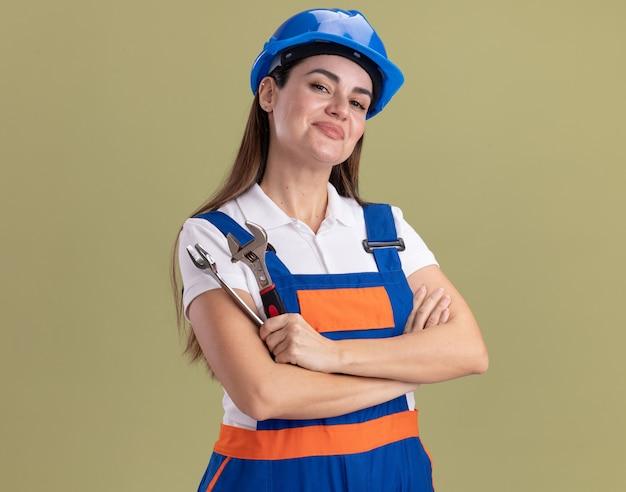 Lieta giovane donna del costruttore in uniforme che tiene le mani incrociate della chiave aperta isolate sulla parete verde oliva