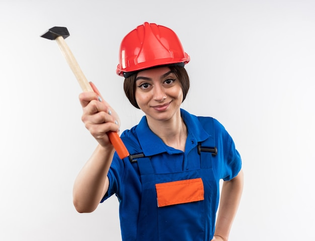 Pleased young builder woman in uniform holding out hammer isolated on white wall