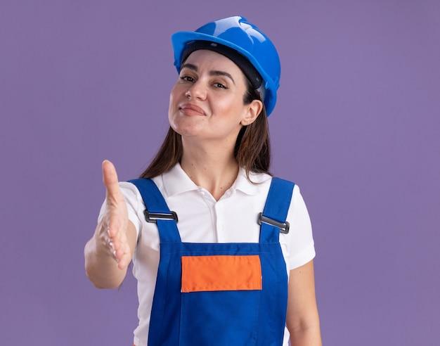 Lieta giovane donna costruttore in uniforme tendendo la mano alla telecamera isolata sulla parete viola