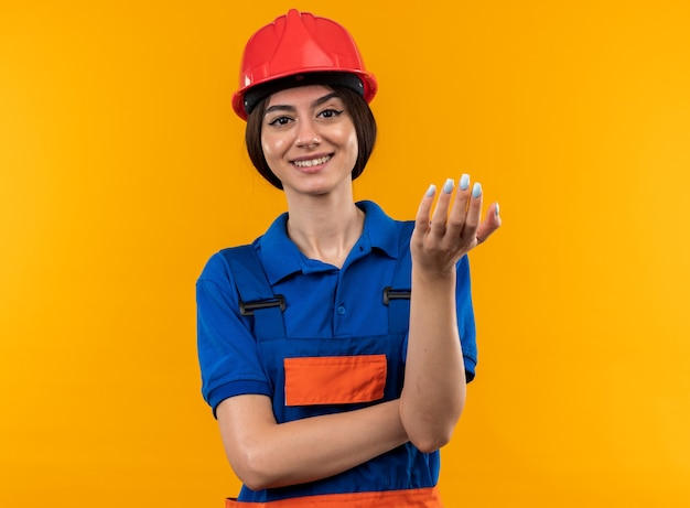 Pleased  young builder woman in uniform holding out hand  isolated on yellow wall