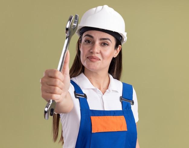 Lieta giovane donna del costruttore in uniforme che tiene fuori la chiave aperta isolata sulla parete verde oliva