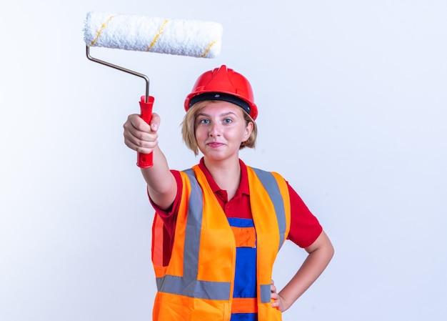Compiaciuta giovane donna builder in uniforme tenendo fuori la spazzola a rullo davanti mettendo la mano sull'anca isolata sul muro bianco