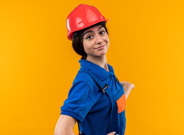 Felice giovane donna costruttore in uniforme isolata sul muro giallo