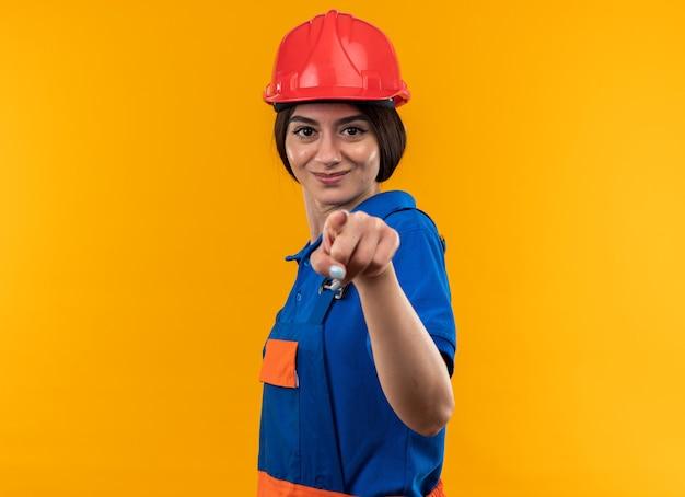 Felice giovane donna costruttore in punti uniformi isolati sul muro giallo