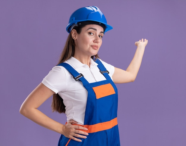 Pleased young builder woman in uniform points with hand at behind isolated on purple wall with copy space