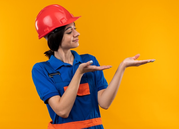 Pleased young builder woman in uniform pretending holding and points at something isolated on yellow wall with copy space