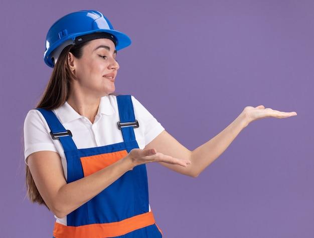 Lieta giovane donna costruttore in uniforme che finge di tenere qualcosa di isolato sulla parete viola con spazio di copia