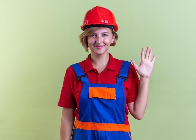 Compiaciuta giovane donna costruttore in uniforme che mostra gesto di saluto isolato su parete verde oliva