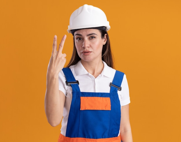 Pleased young builder woman in uniform showing peace gesture isolated on orange wall