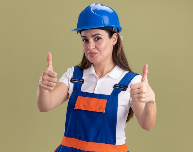 Pleased young builder woman in uniform showing thumbs up isolated on olive green wall