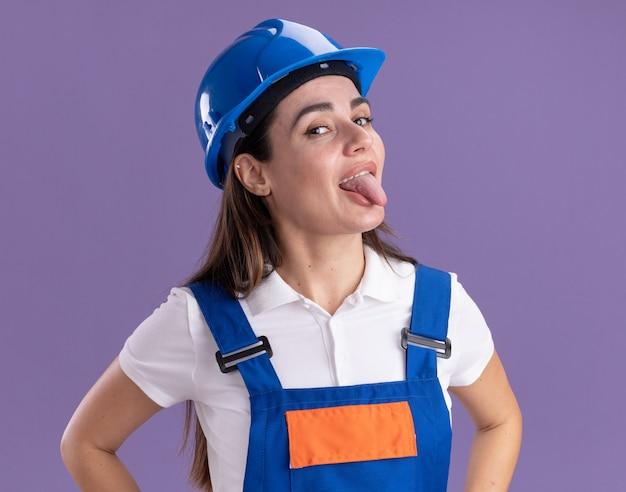 Felice giovane donna costruttore in uniforme che mostra la lingua isolata sul muro viola