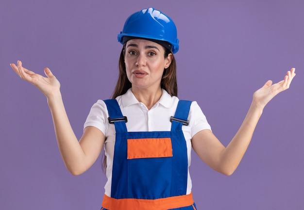 Lieta giovane donna costruttore in uniforme diffondendo le mani isolate sulla parete viola