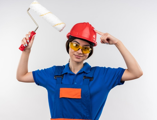 Pleased young builder woman in uniform with glasses holding roller brush putting finger on head