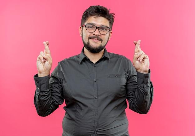 Довольный молодой бизнесмен в очках и скрестив пальцы, изолированные на розовой стене