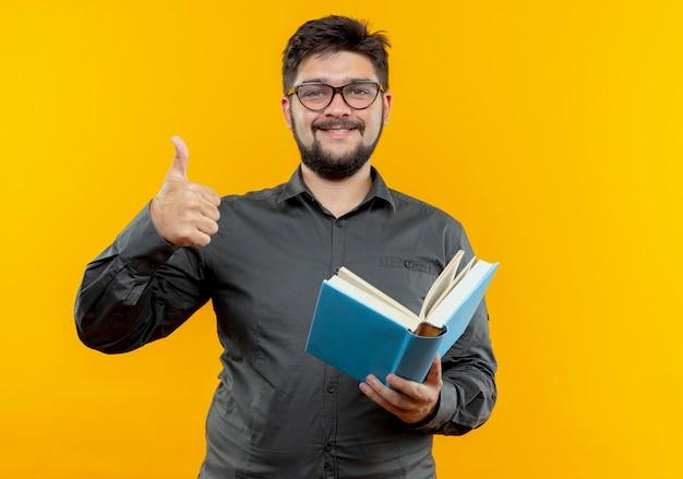 노란색 배경에 고립 책 그의 엄지 손가락을 들고 안경을 쓰고 기쁘게 젊은 사업가