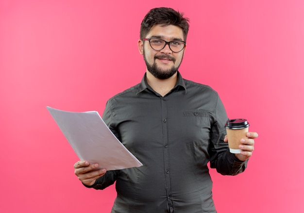 ピンクの壁に隔離されたコーヒーと紙のカップを保持している眼鏡をかけている若いビジネスマンを喜ばせる