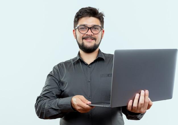 白い背景で隔離のラップトップを保持している眼鏡をかけている若いビジネスマンを喜ばせる