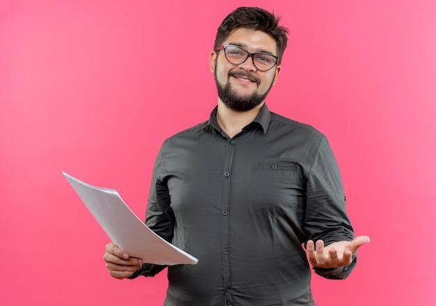Довольный молодой бизнесмен в очках держит бумагу и протягивает руку, изолированную на розовой стене