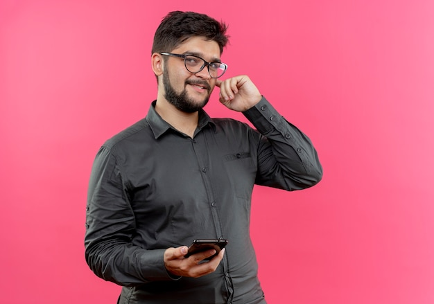 Pleased young businessman wearing glasses holding phone putting finger on ear isolated on pink wall