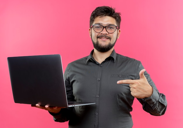 Pleased young businessman wearing glasses holding and points at laptop isolated on pink wall