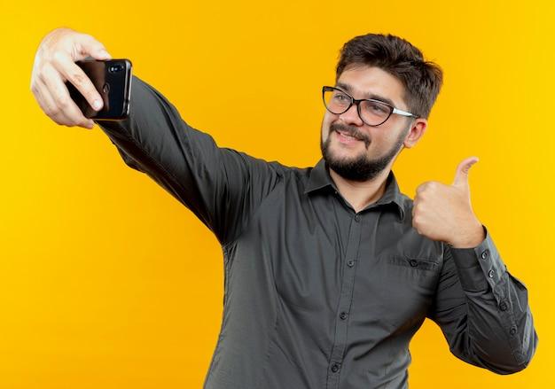 안경을 착용 기쁘게 젊은 사업가 노란색 배경에 고립 된 자신의 엄지 손가락을 셀카 걸릴