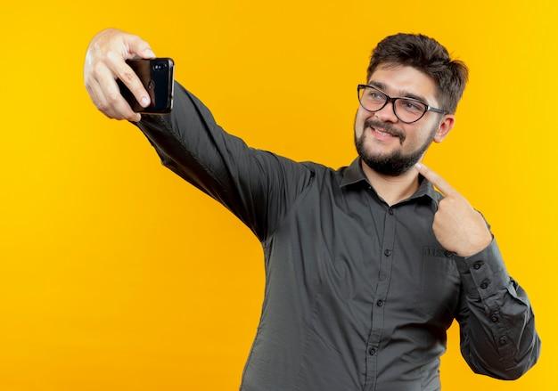 Lieto giovane imprenditore con gli occhiali prende un selfie e indica se stesso