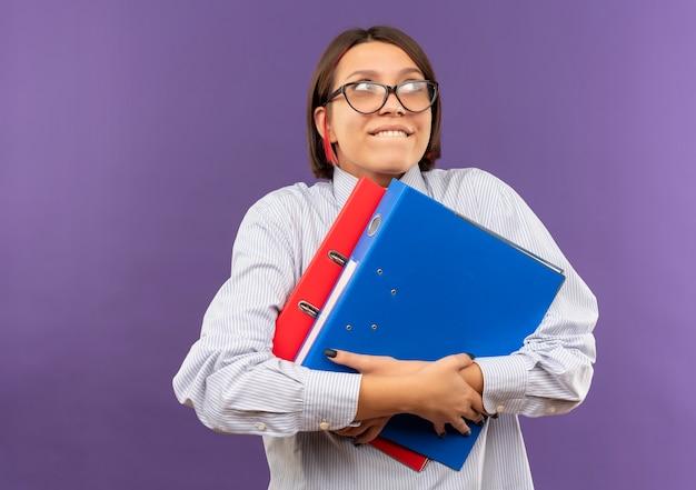 Lieta giovane ragazza del call center con gli occhiali che tengono le cartelle guardando il lato isolato su sfondo viola con spazio di copia