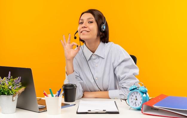 Довольная молодая девушка call-центра в гарнитуре сидит за столом и делает знак ок, изолированные на оранжевом фоне