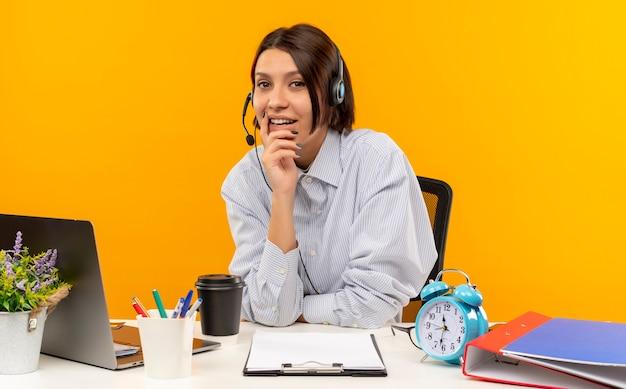Довольная молодая девушка call-центра в гарнитуре сидит за столом, положив руку на подбородок, изолированную на оранжевом фоне