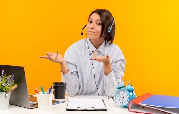 Довольная молодая девушка call-центра в гарнитуре сидит за столом, показывая пустые руки, изолированные на оранжевом фоне
