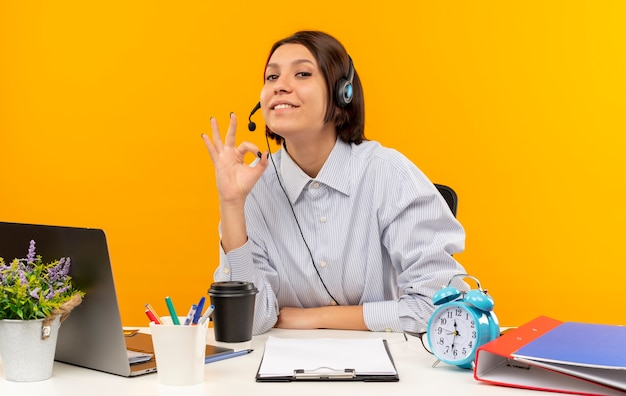 Pleased young call center girl wearing headset sitting at desk doing ok sign isolated on orange background