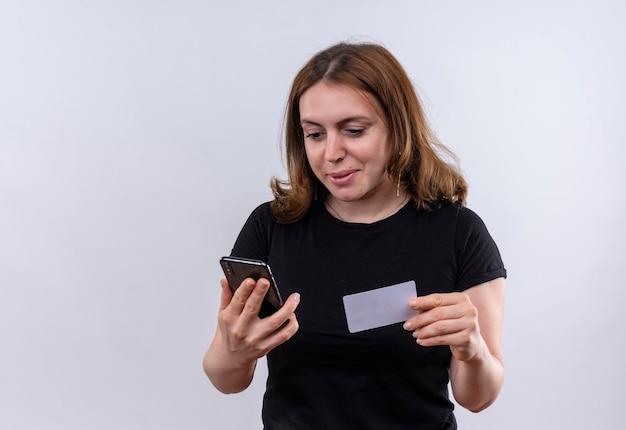 コピースペースと隔離された白いスペースに携帯電話とクレジットカードを保持している若いカジュアルな女性を喜ばせる