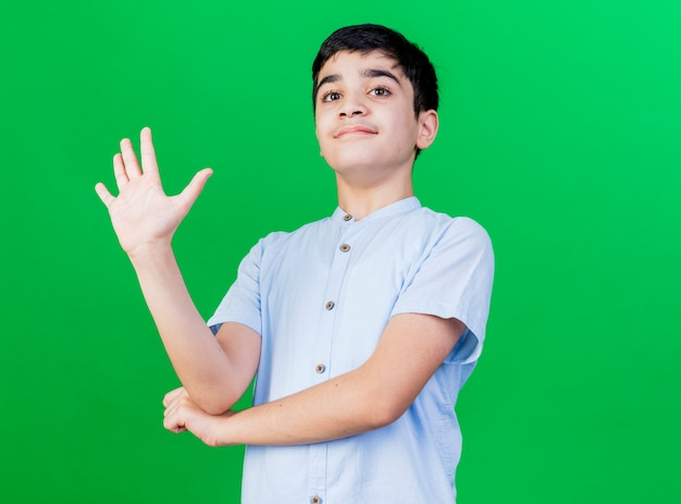 Pleased young caucasian boy looking at camera keeping hand under elbow showing five with hand isolated on green background with copy space