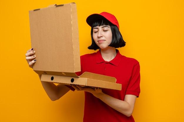 피자 상자를 들고 킁킁 거리며 기쁘게 젊은 백인 배달 소녀