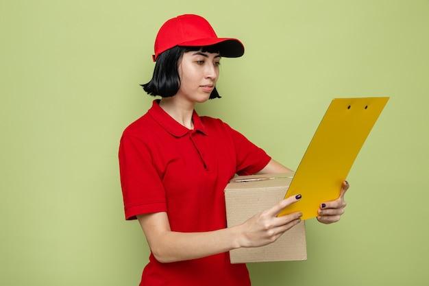 Lieta giovane ragazza delle consegne caucasica che tiene in mano una scatola di cartone e appunti