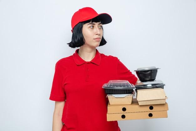 Lieta giovane ragazza delle consegne caucasica che tiene in mano contenitori per alimenti e imballaggi su scatole per pizza guardando a lato
