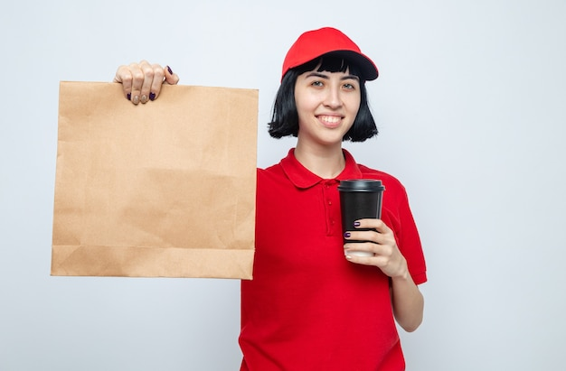 Pleased young caucasian delivery girl holding food packaging and paper cup looking at front