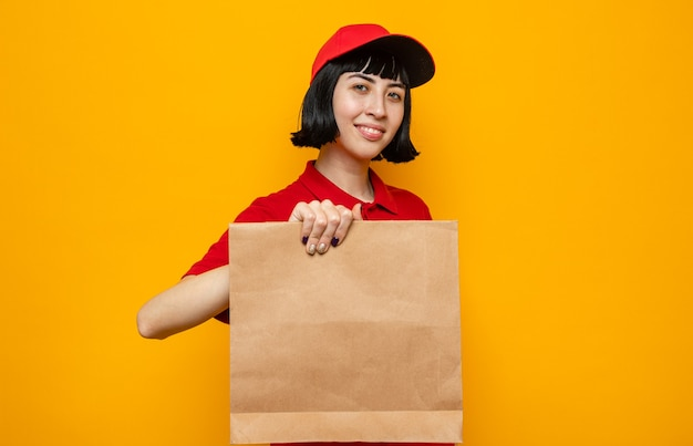 Pleased young caucasian delivery girl holding paper food packaging