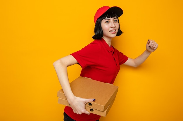 Pleased young caucasian delivery girl standing sideways holding pizza boxes and pretending to run
