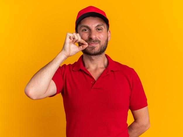 Довольный молодой кавказский курьер в красной форме и кепке держит руку за спиной, закрывая рот