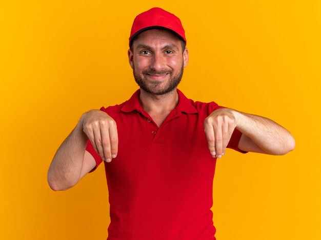 Довольный молодой кавказский курьер в красной форме и кепке, смотрящий в камеру, притворяется, что держит что-то изолированное на оранжевой стене