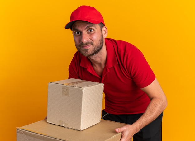 Pleased young caucasian delivery man in red uniform and cap bending down keeping hands on cardboard box looking at camera isolated on orange wall