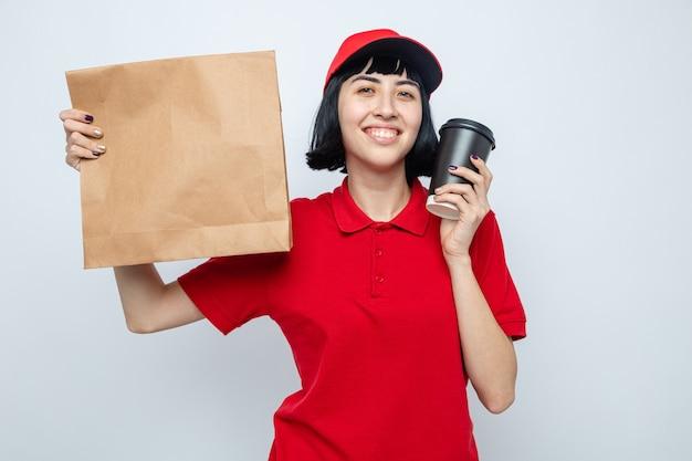 Soddisfatta giovane donna delle consegne caucasica che tiene in mano imballaggi per alimenti e bicchiere di carta