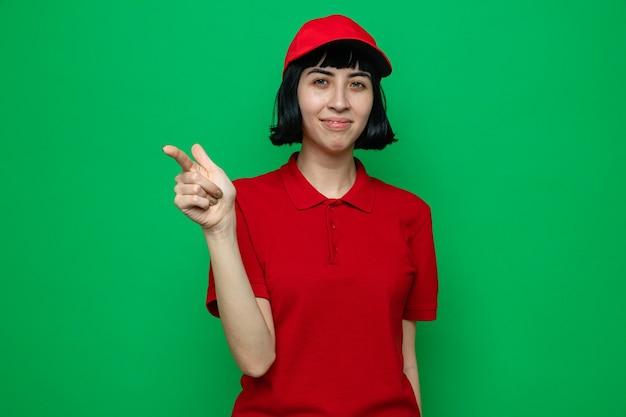 Lieta giovane donna di consegna caucasica che indica a lato