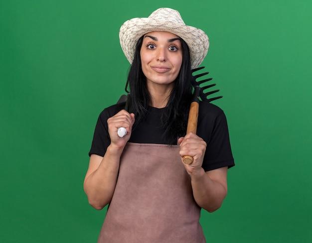 어깨에 갈퀴와 괭이 갈퀴를 들고 유니폼과 모자를 쓰고 기쁘게 젊은 백인 정원사 소녀