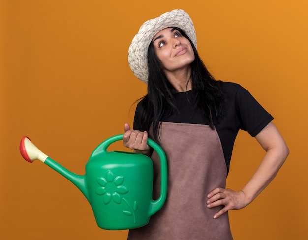 Pleased young caucasian gardener girl wearing uniform and hat holding watering can keeping hand on waist looking up isolated on orange wall