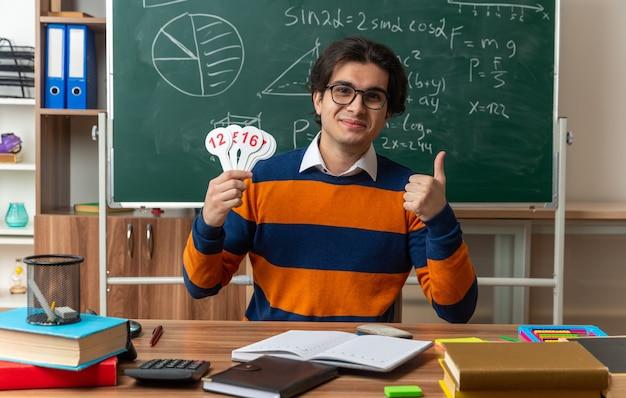 Contento giovane insegnante di geometria caucasica con gli occhiali seduto alla scrivania con materiale scolastico in aula che mostra il numero di fan e pollice in alto guardando davanti